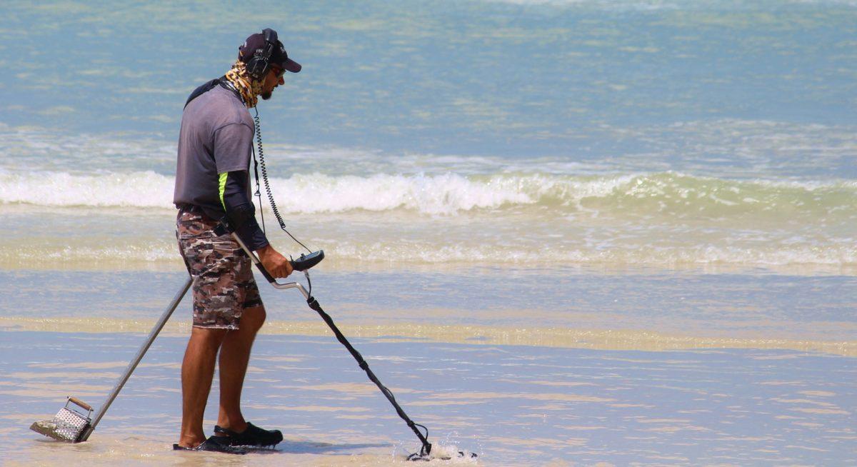 På skattejagt med metaldetektor ved stranden.