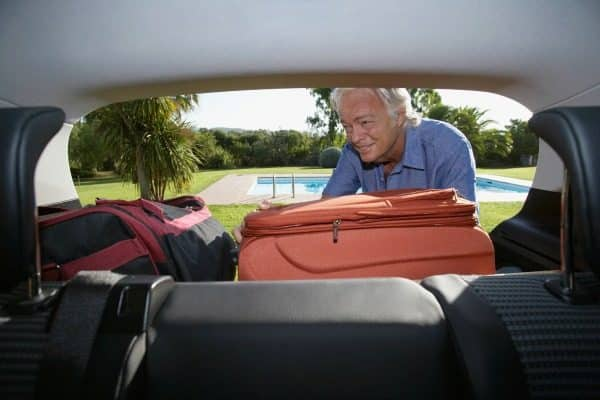 Senior man putting luggage into car boot